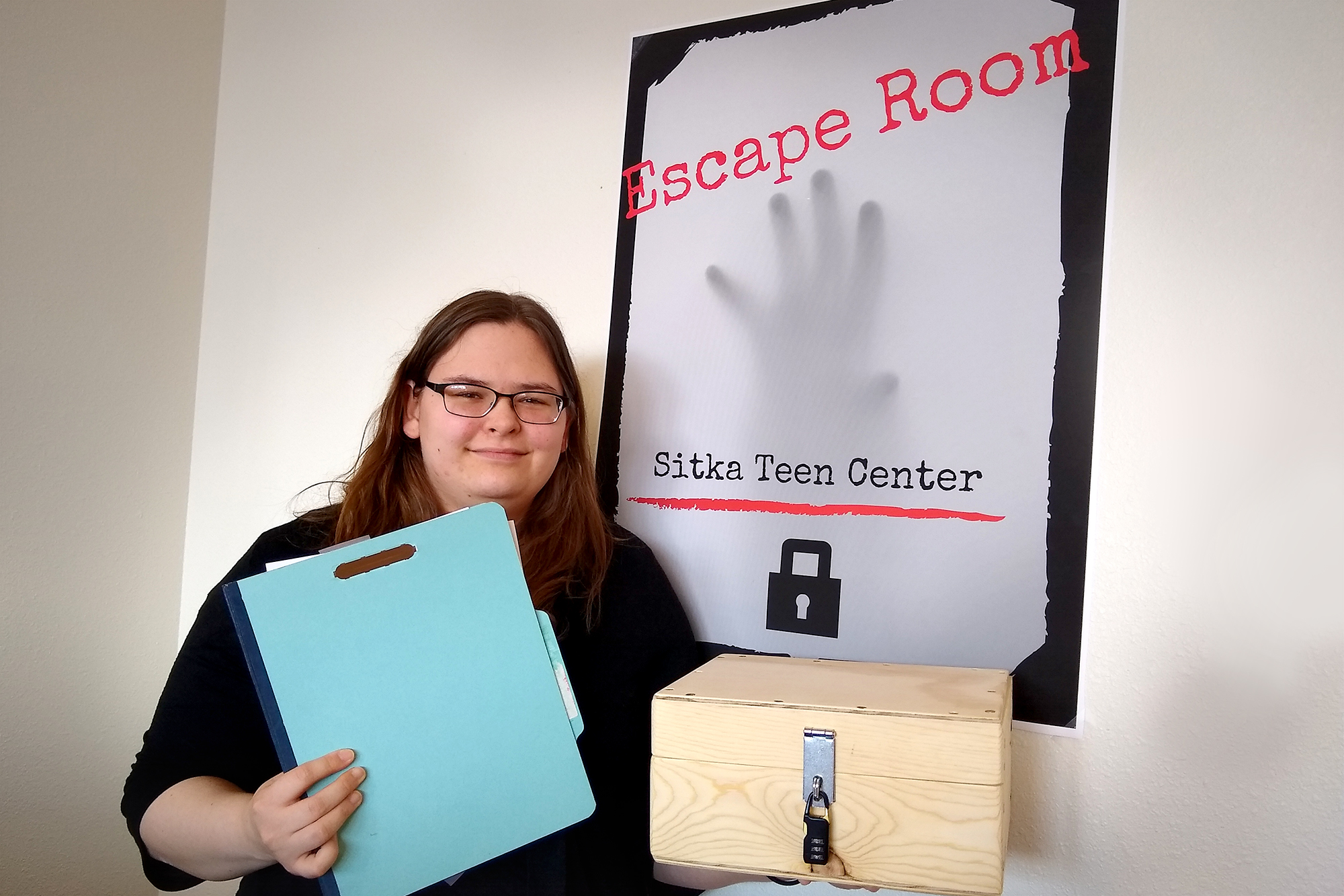 Event organizer Gabriella Barile holds up a folder and locked, wooden box from the hospital-themed escape room.