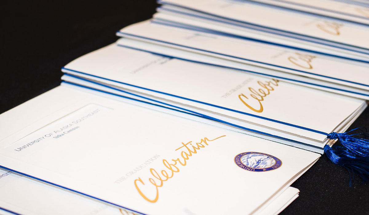 Programs for graduation ceremony spread out on table.